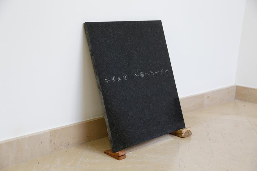Repertory (ideograms), 2016, sandblast on granite, wood (guayacan) rubber, 50 x 50cm.